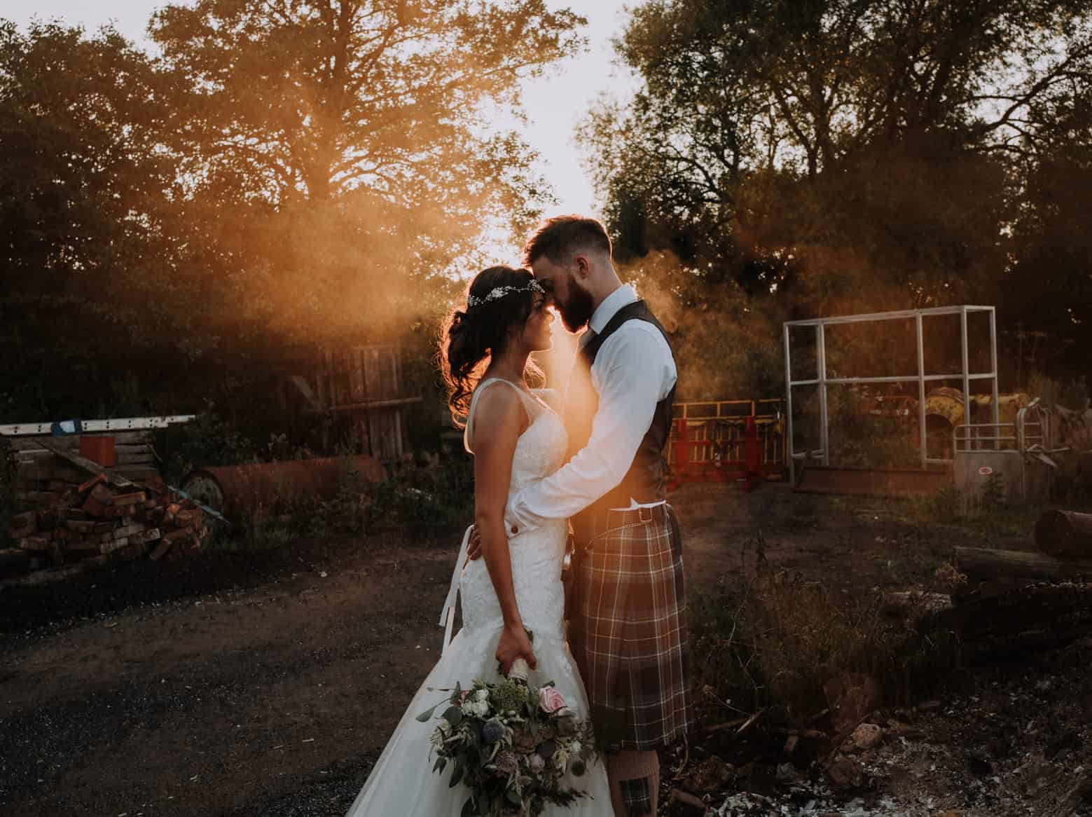 Bride and groom backlit by the sun and smoky