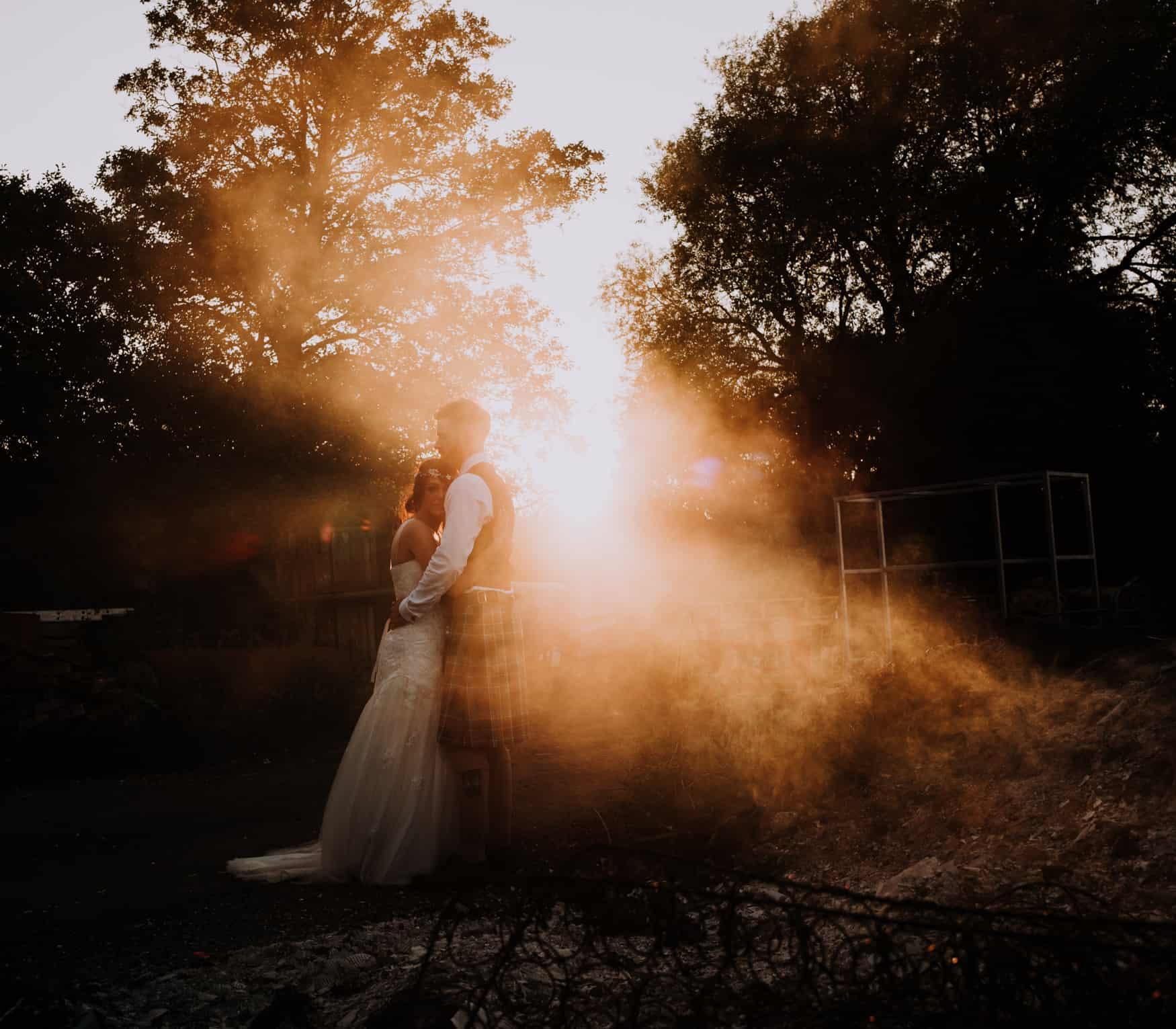 Bride and groom sunset with smoke