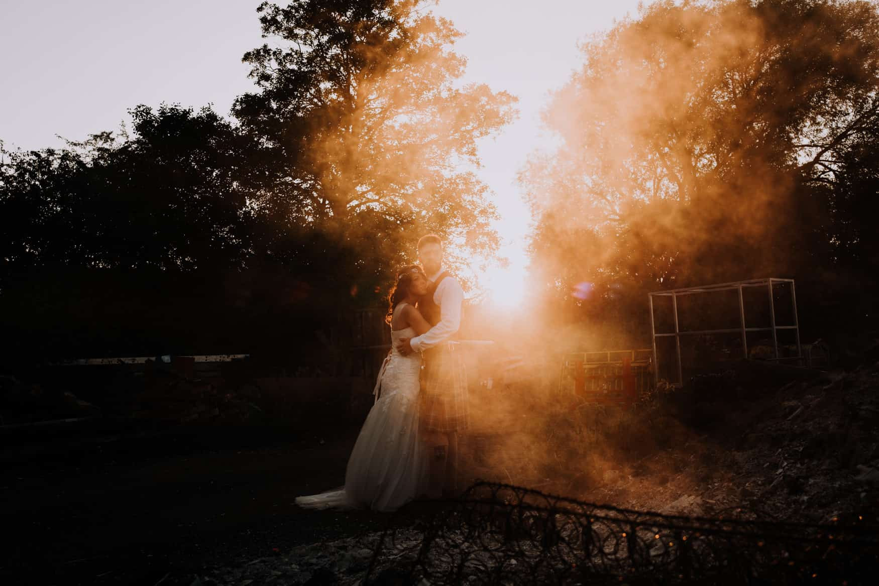 Bride and groom sunset with bonfire shot