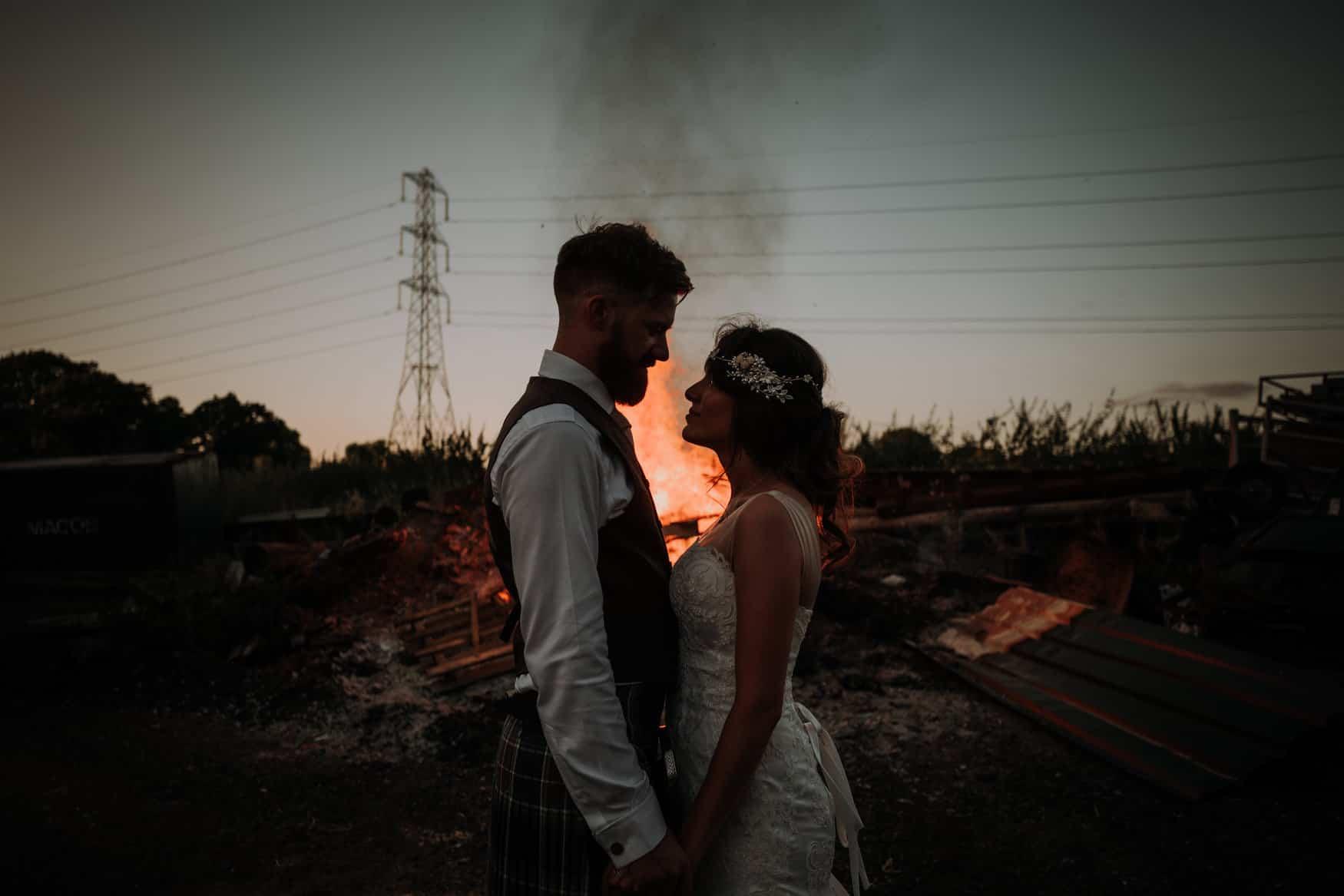 bride and groom portrait next to a bonfire