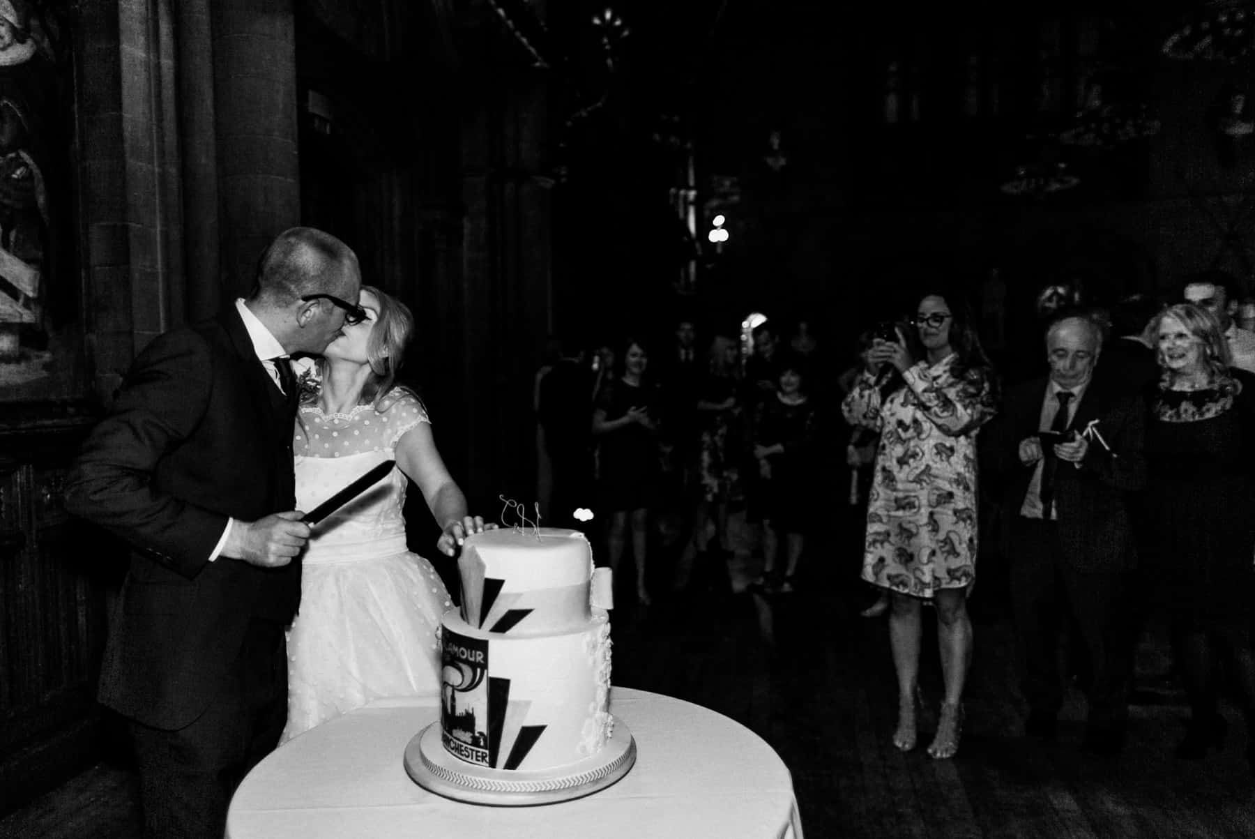 bride and groom cut the cake at manchester town hall