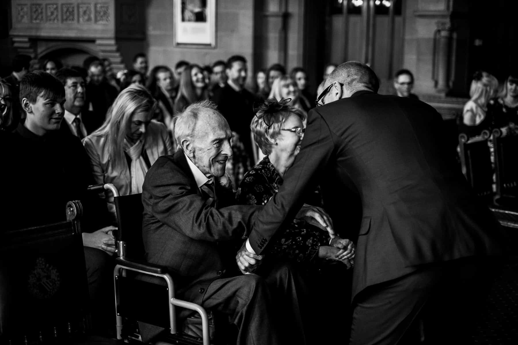 Grandfather and groom share a tender moment