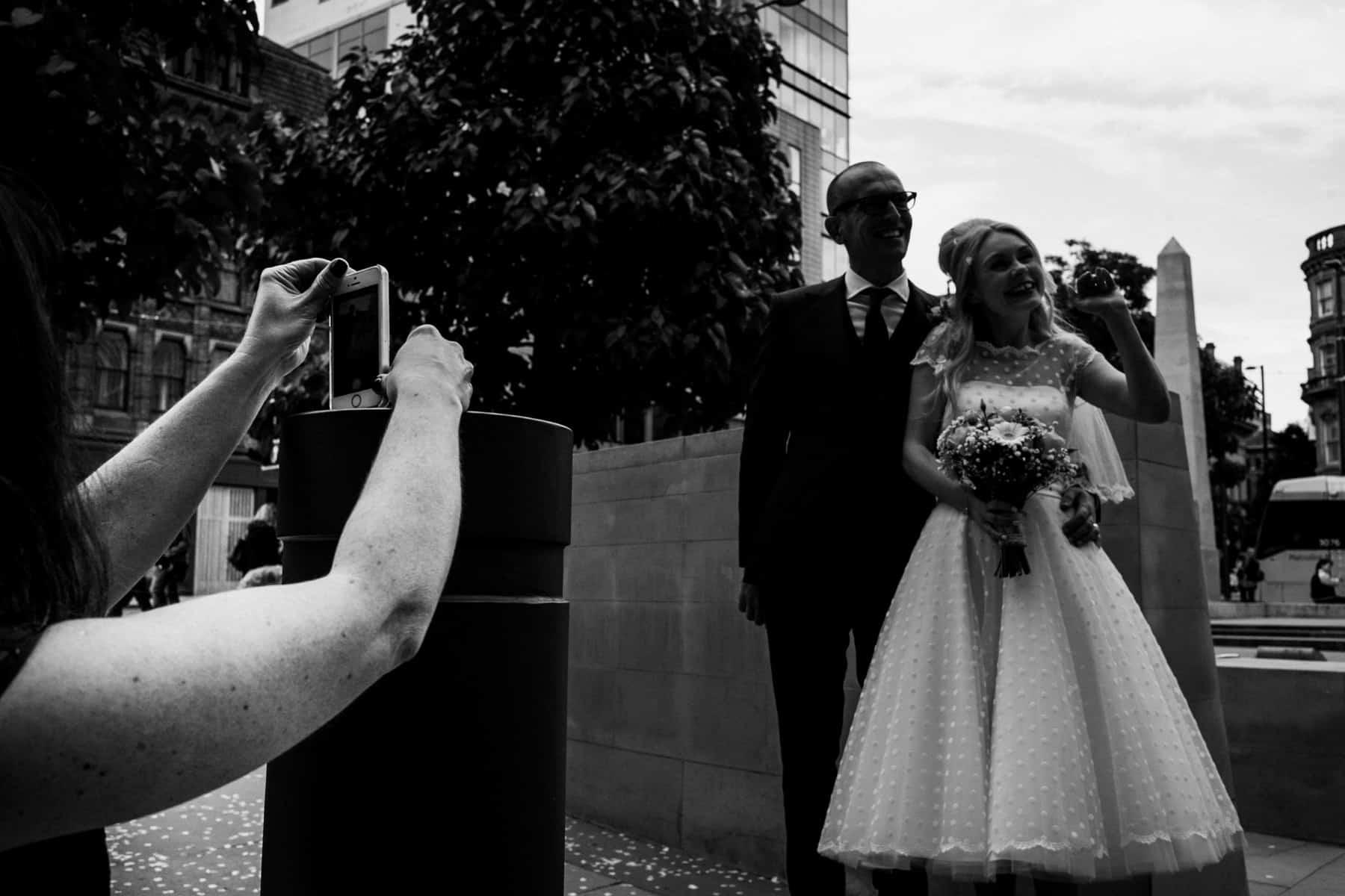 public taking photographs of wedding couple