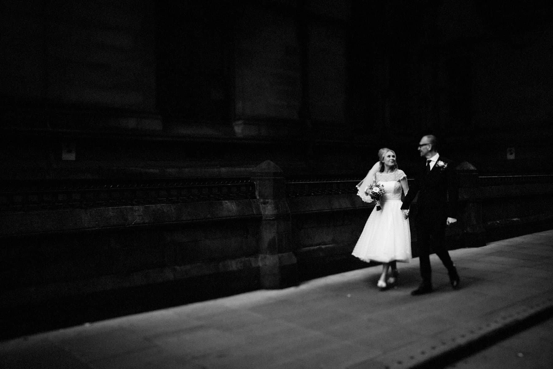 bride and grrom walk through the streets of manchester