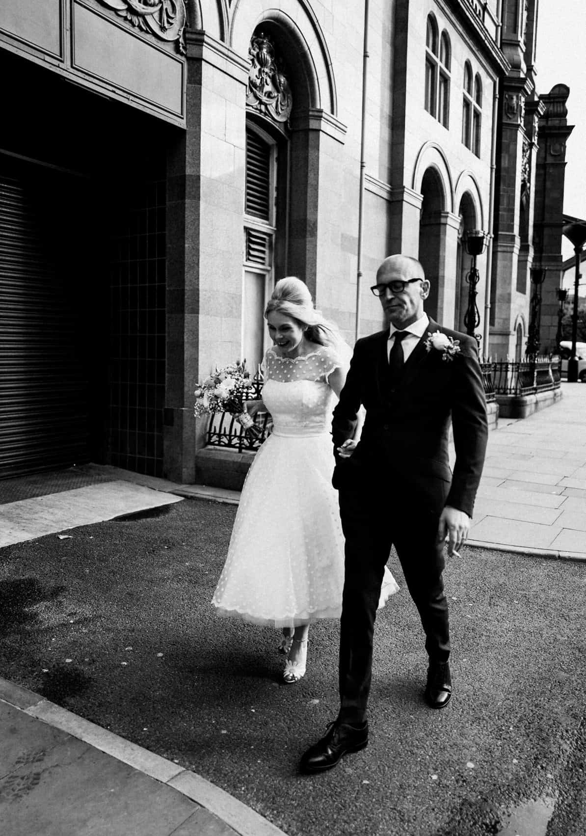 Bride and groom walking through manchester at night