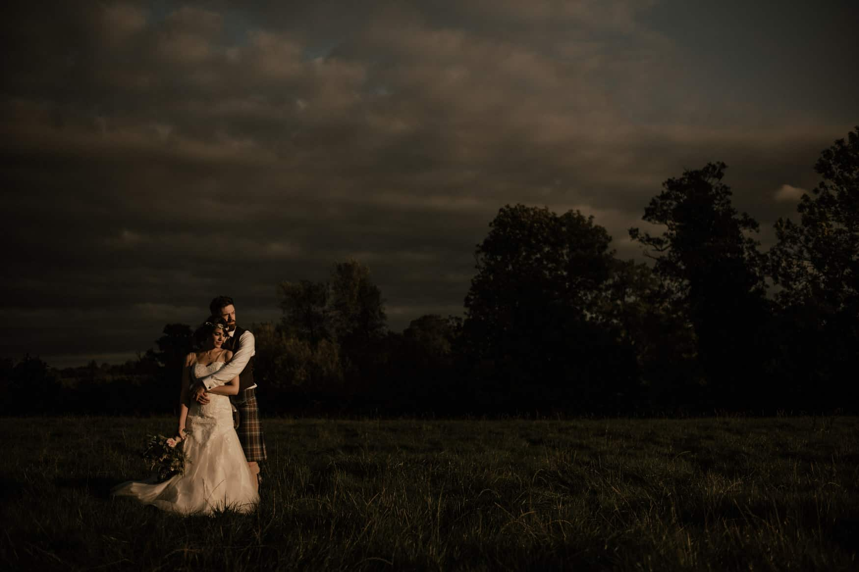 bride and groom portrait in a field