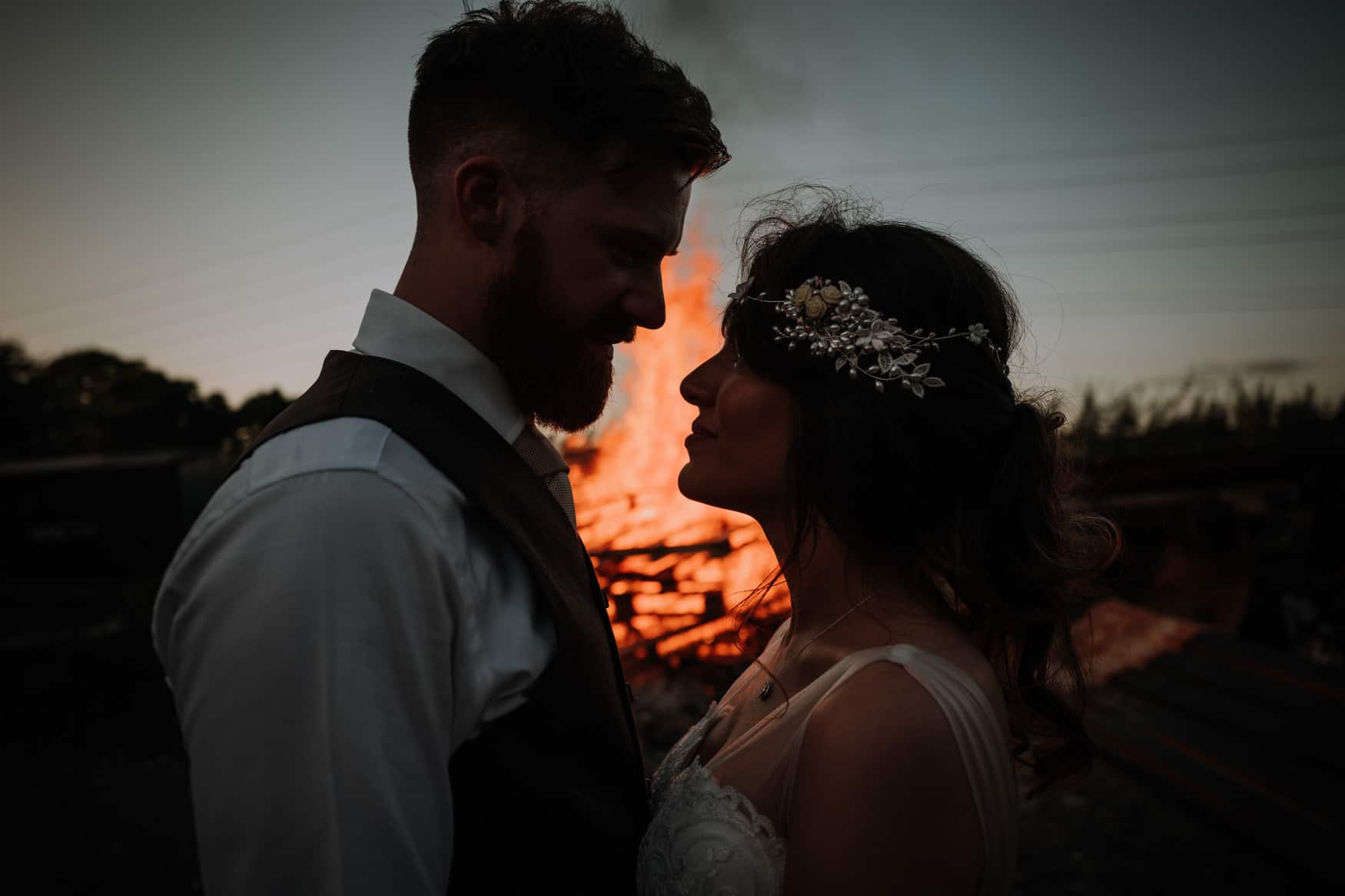 bride and groom portrait in front of a fire