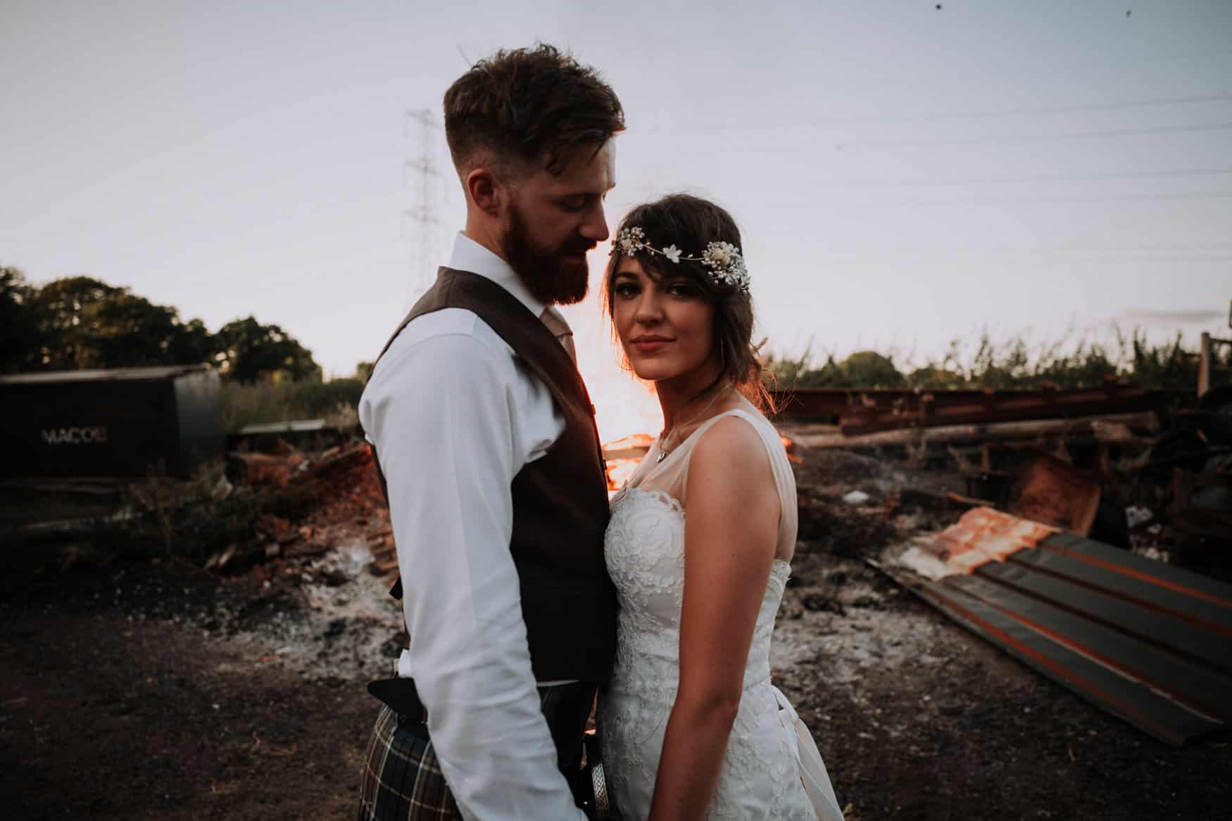 bride and groom portrait backlit by a fire