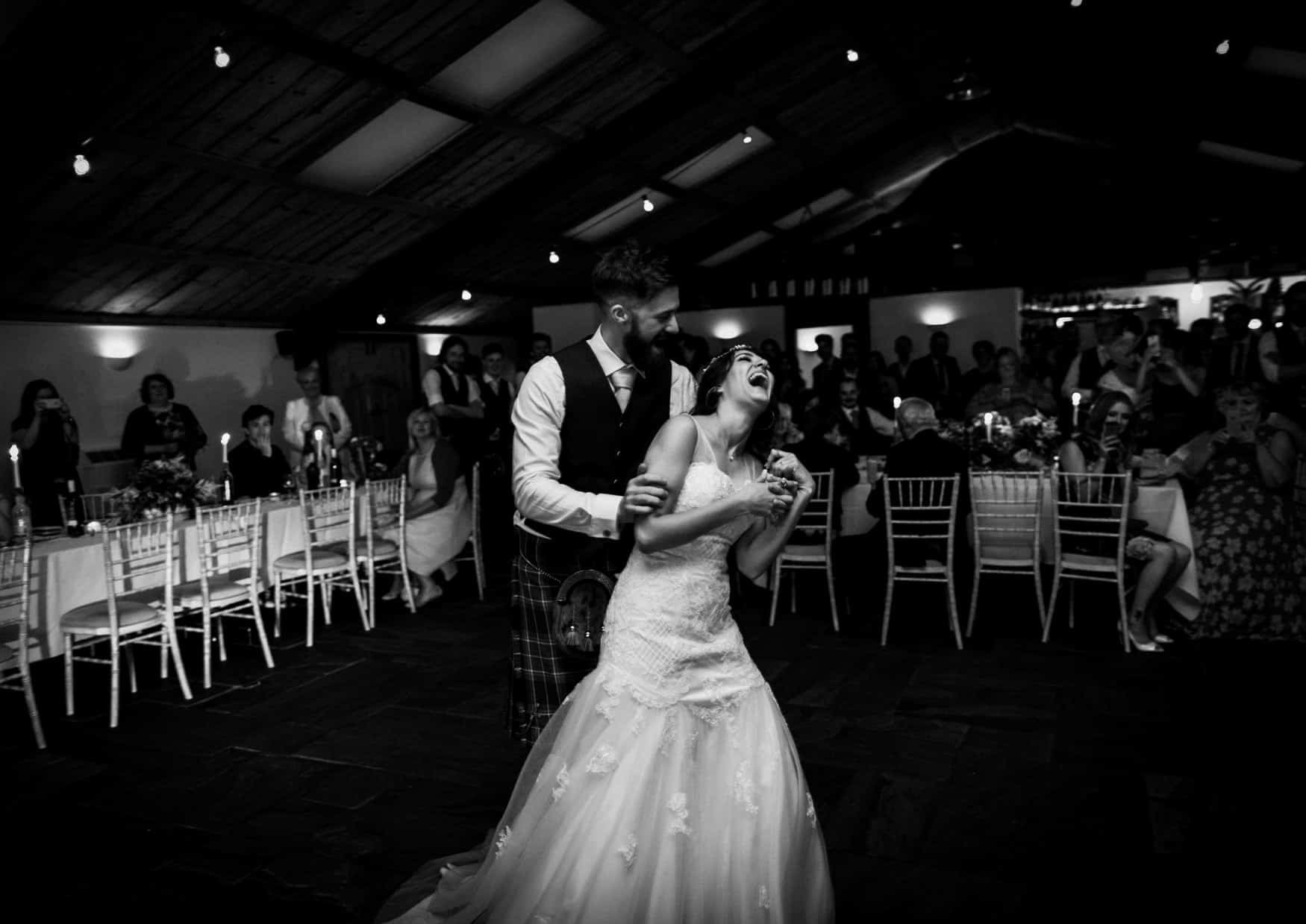 Bride and groom laughter at first dance