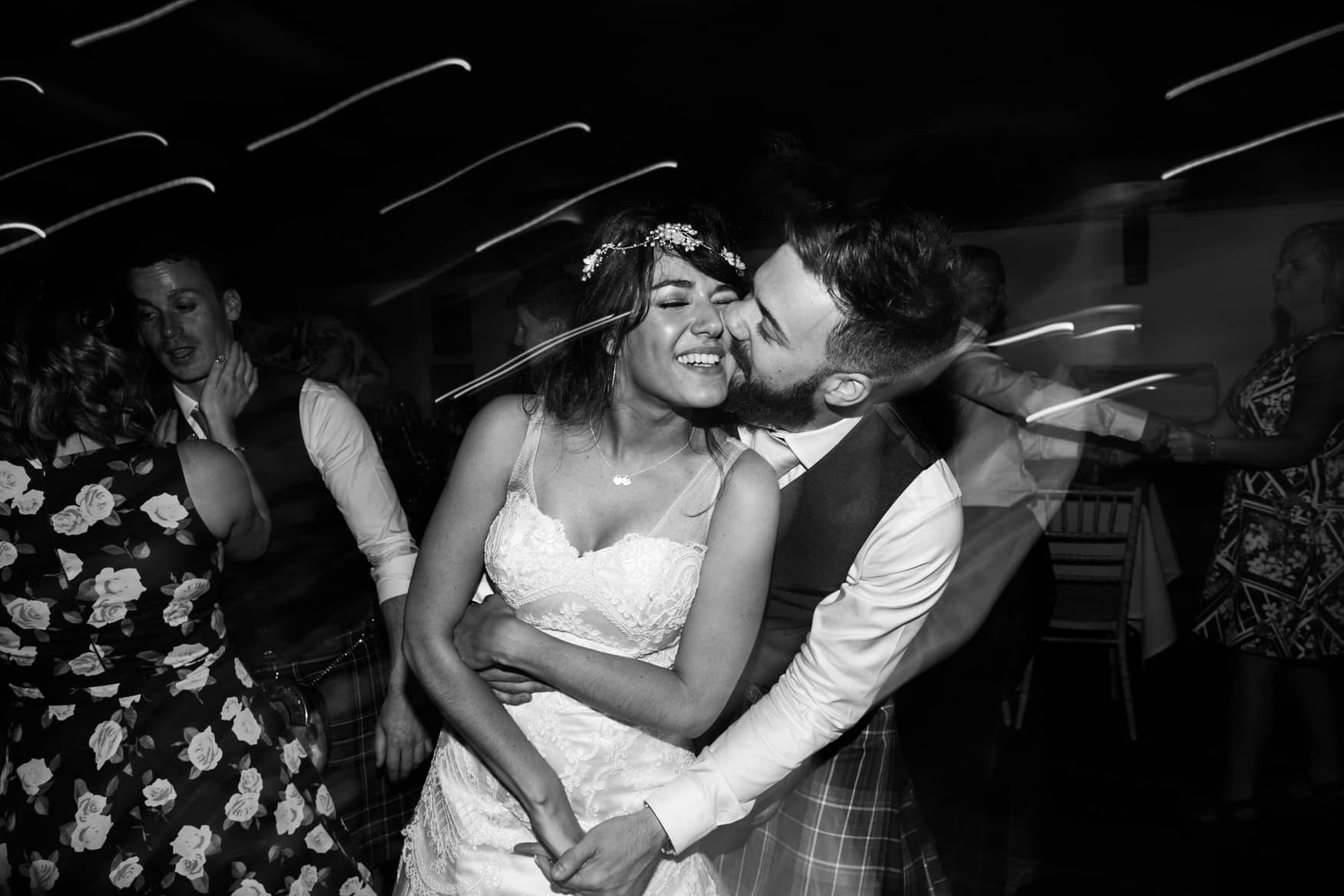 Bride and groom kiss at first dance at Owen House wedding barn