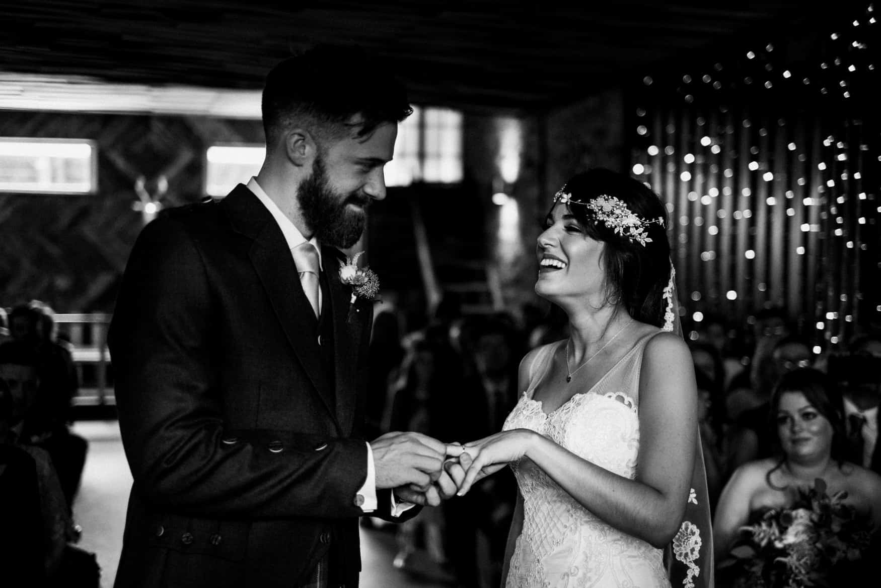 bride and groom laugh at swapping rings