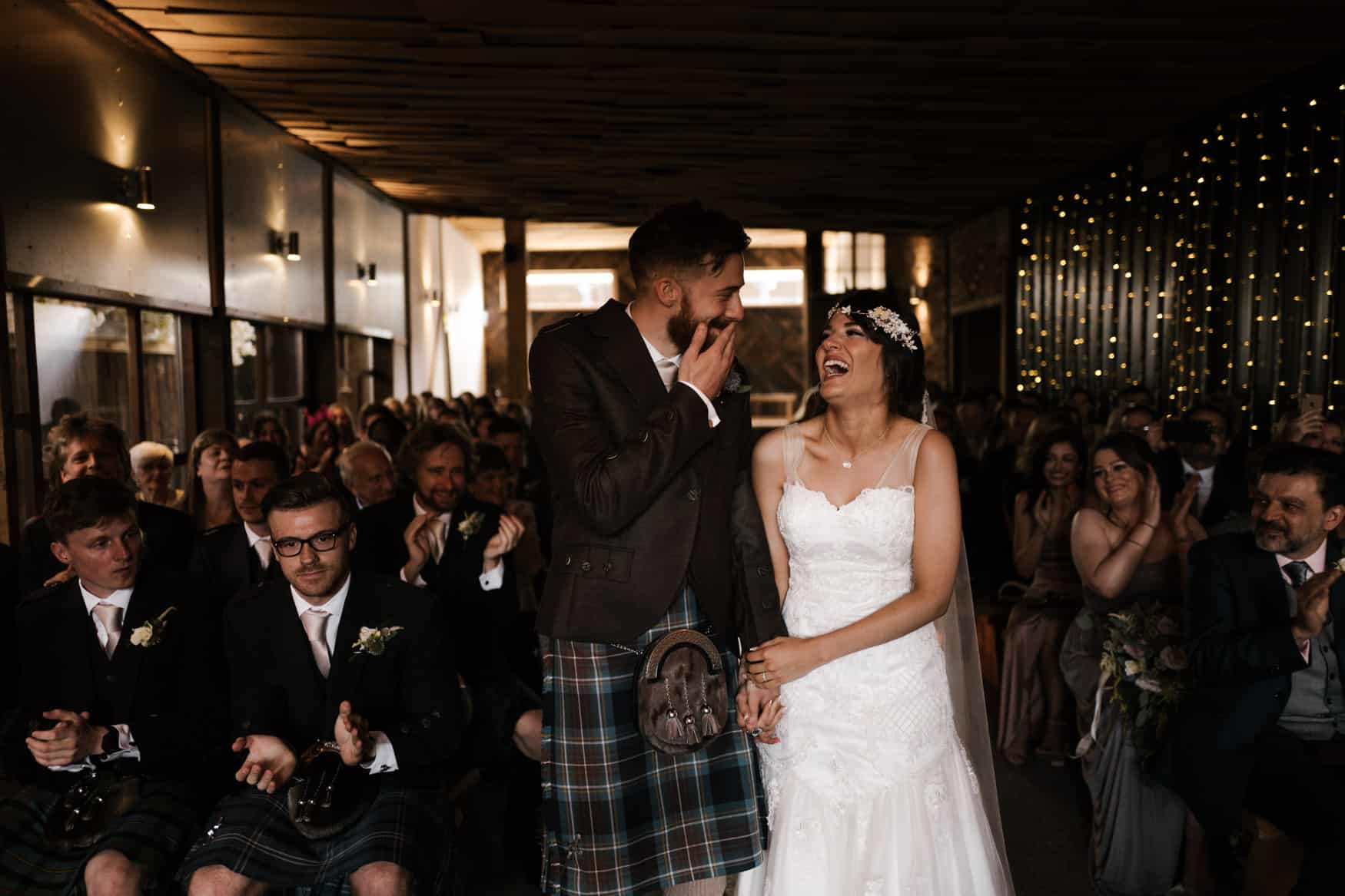 bride and groom laugh at first kiss