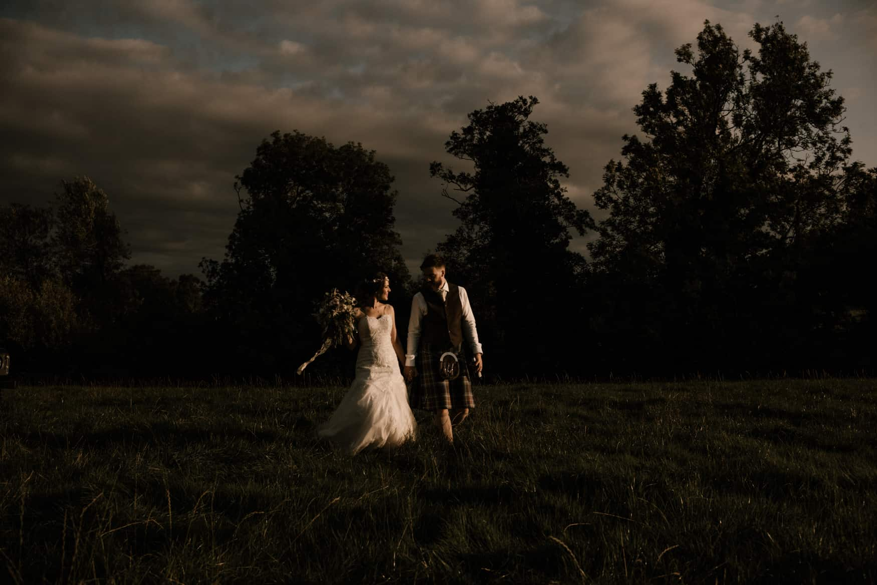 bride and groom walking in field backlit by the sun