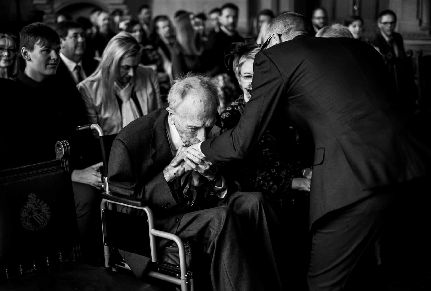 Grandfather kisses grooms hand