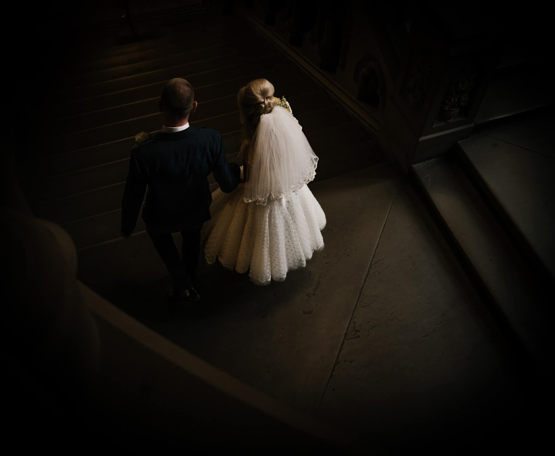 bride and groom walking down manchester town hall steps