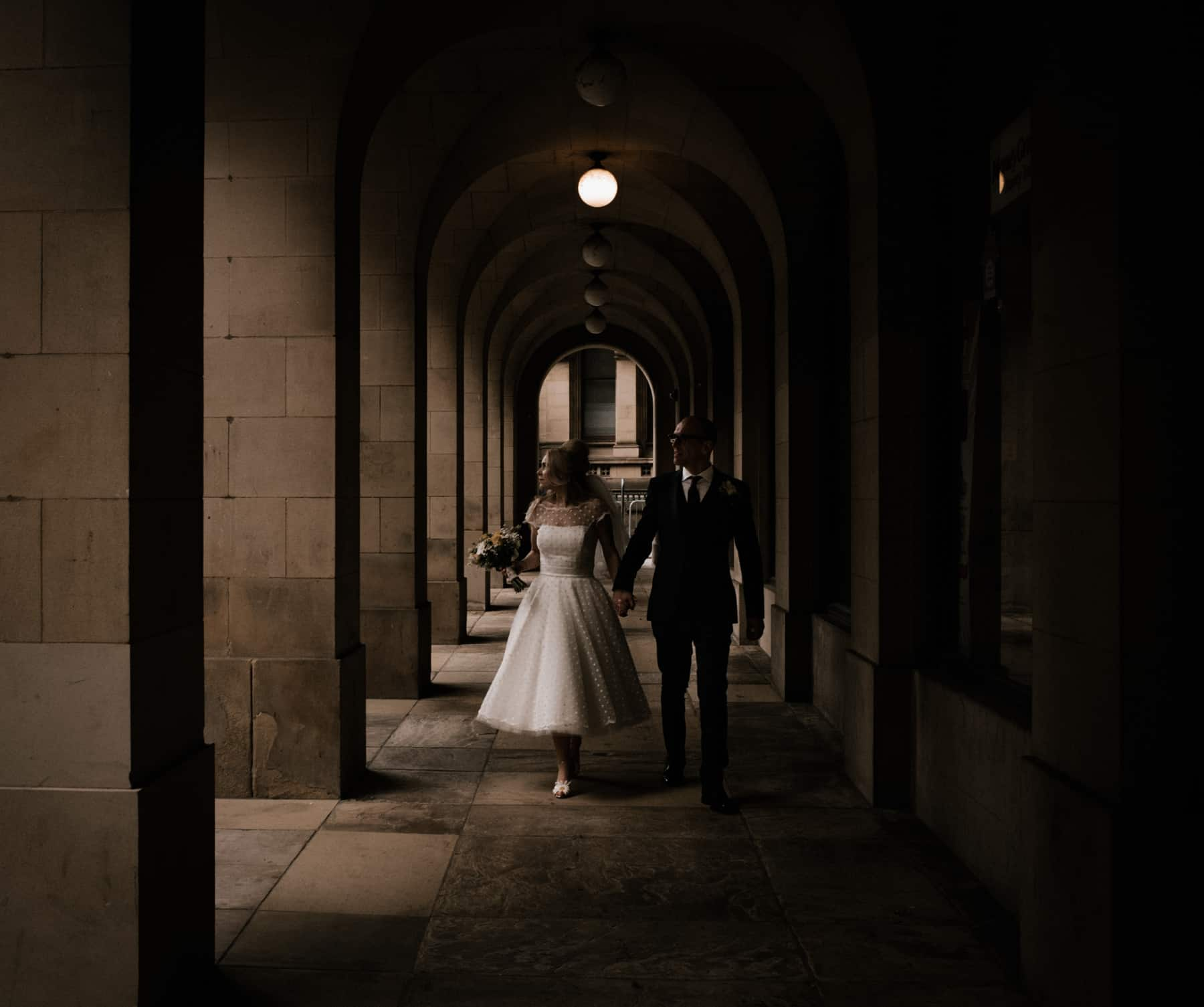 bride and grrom walking outside manchester town hall