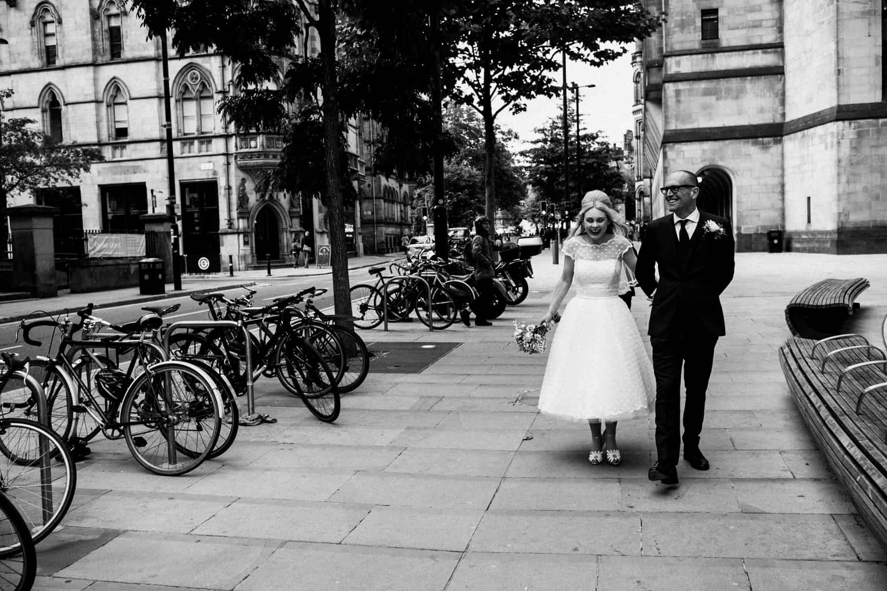 black and white shot of bride and groom walking
