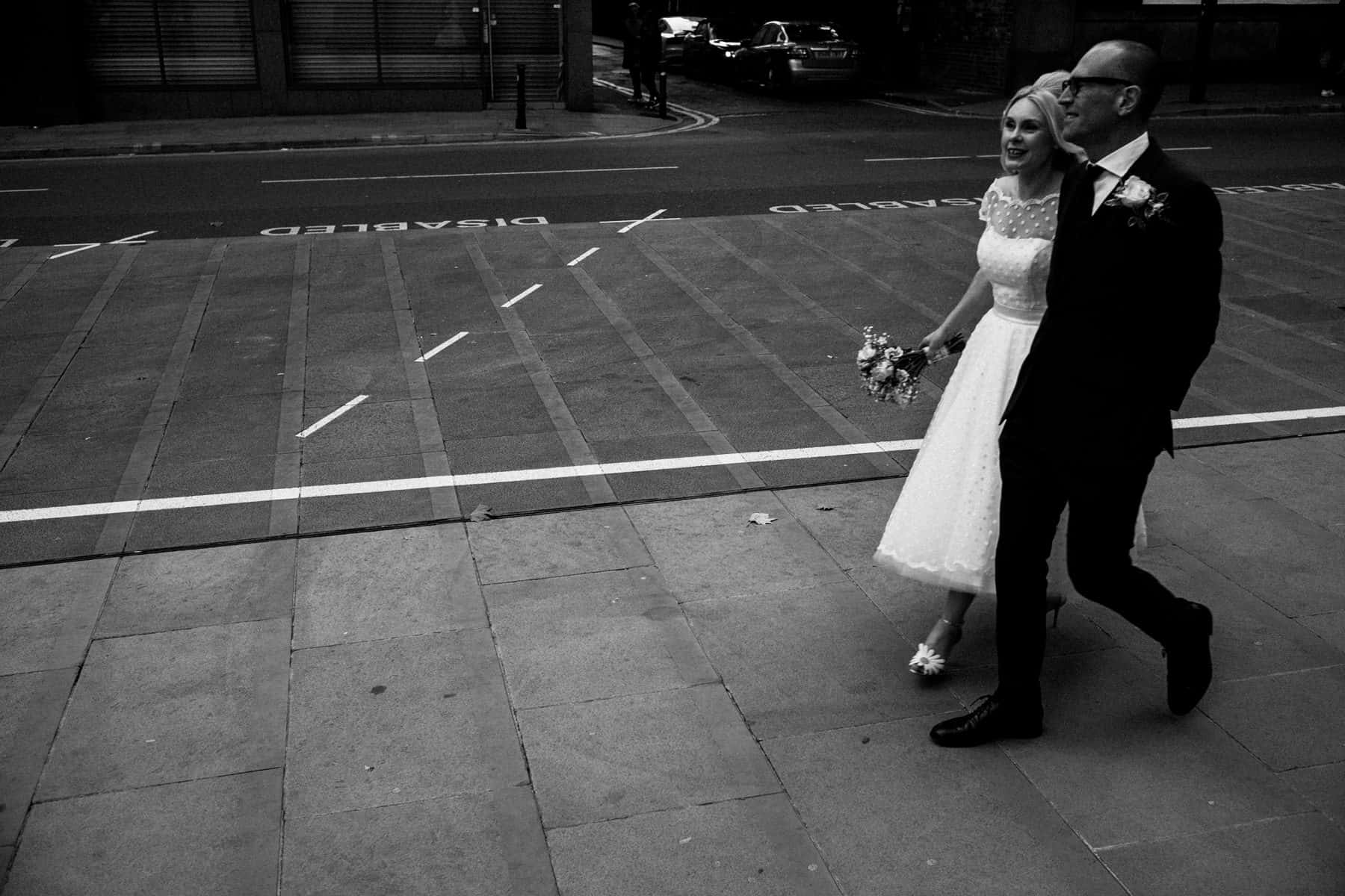 Bride and groom walking amongst the manchester public