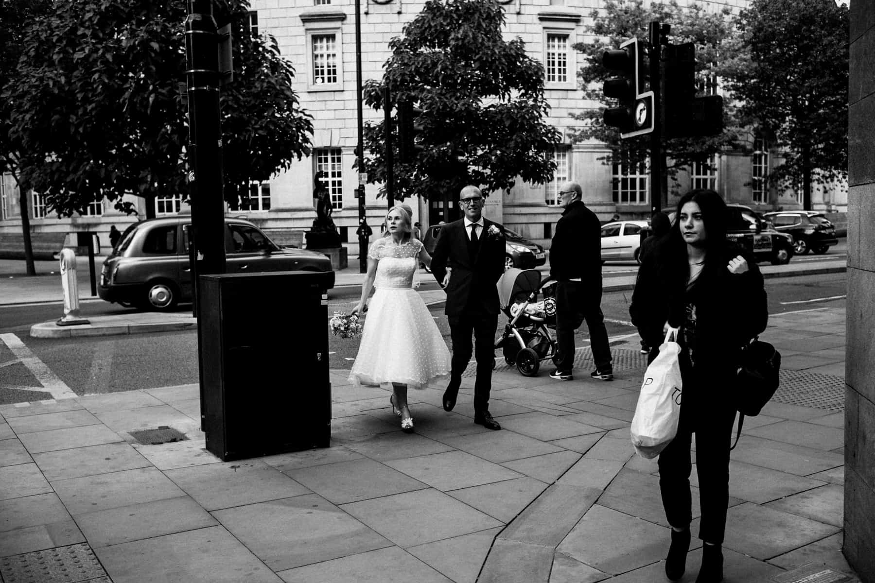 b;ack and white image of bride and groom walking through manchester