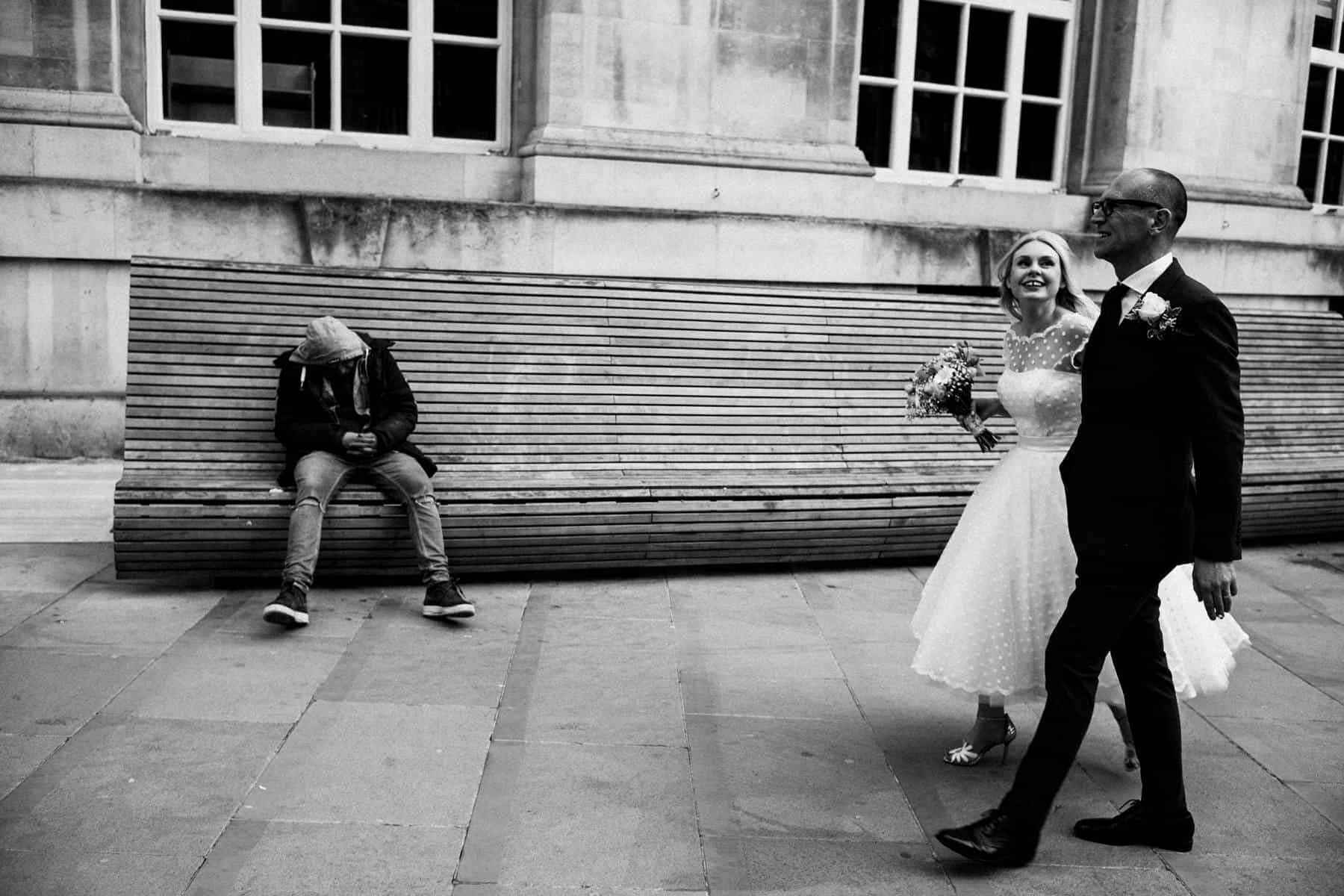 bride and groom walk past homeless man