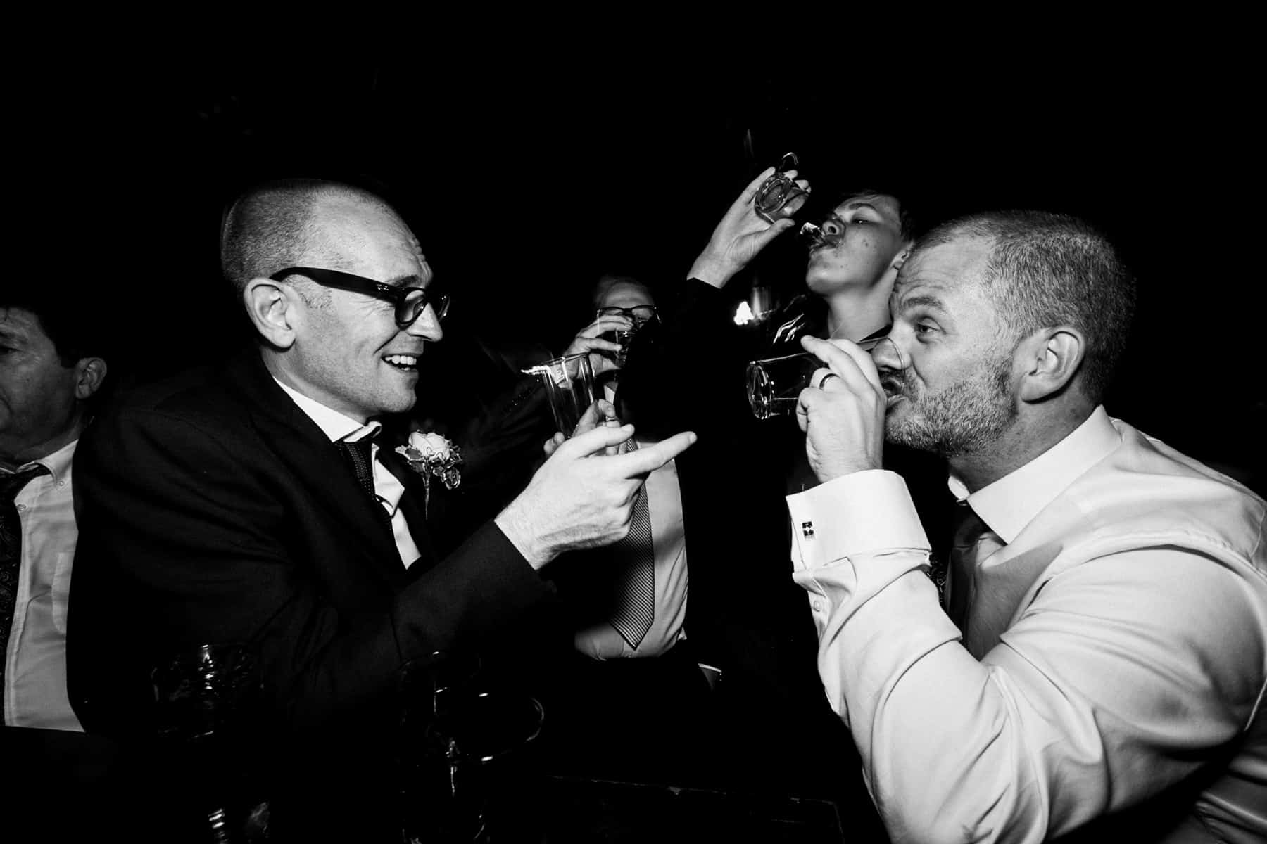 groom and ushers doing shots