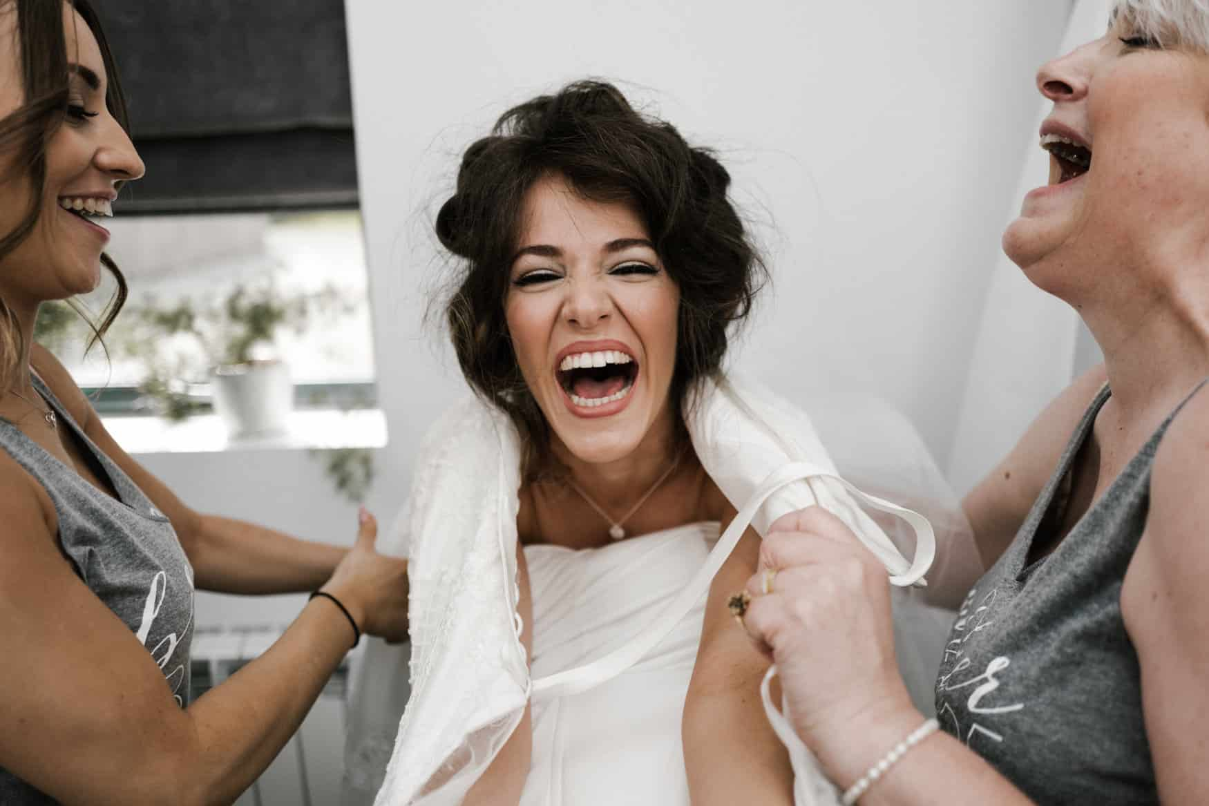bride laughing getting into her dress