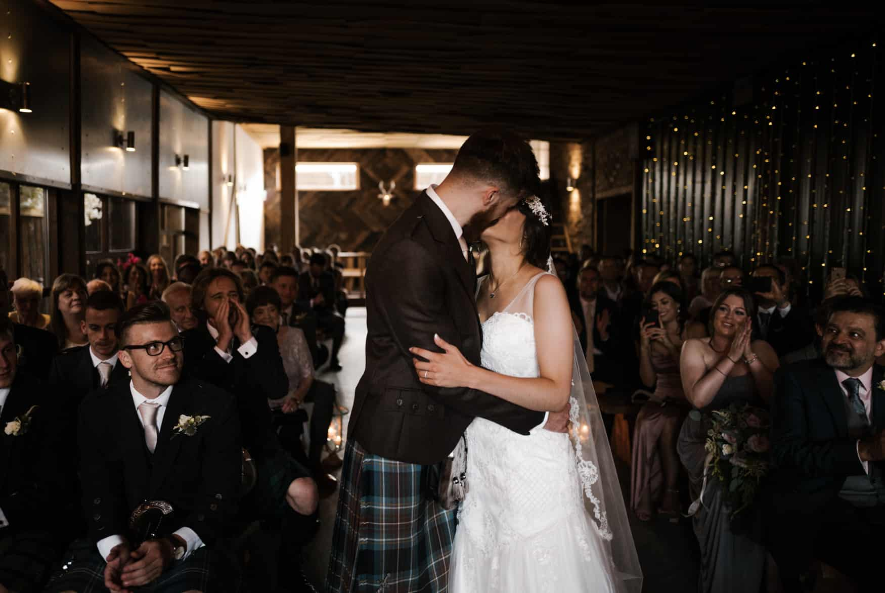 bride and groom first kiss at owen house wedding barn