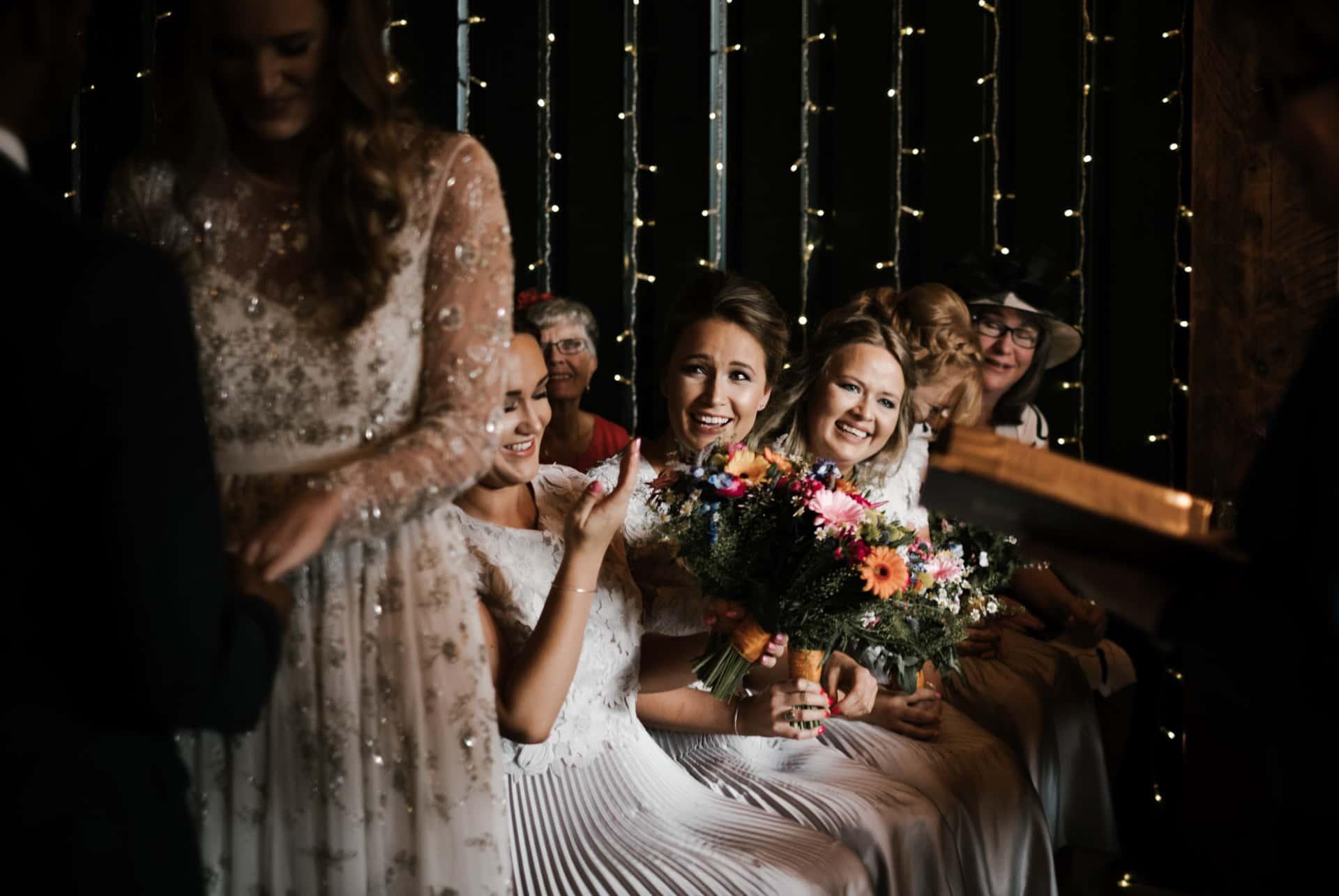 bridesmaids laugh during ceremony