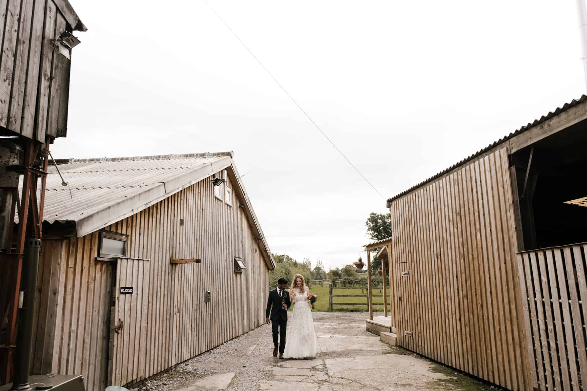 bride and groom walk at Owen House barn wedding