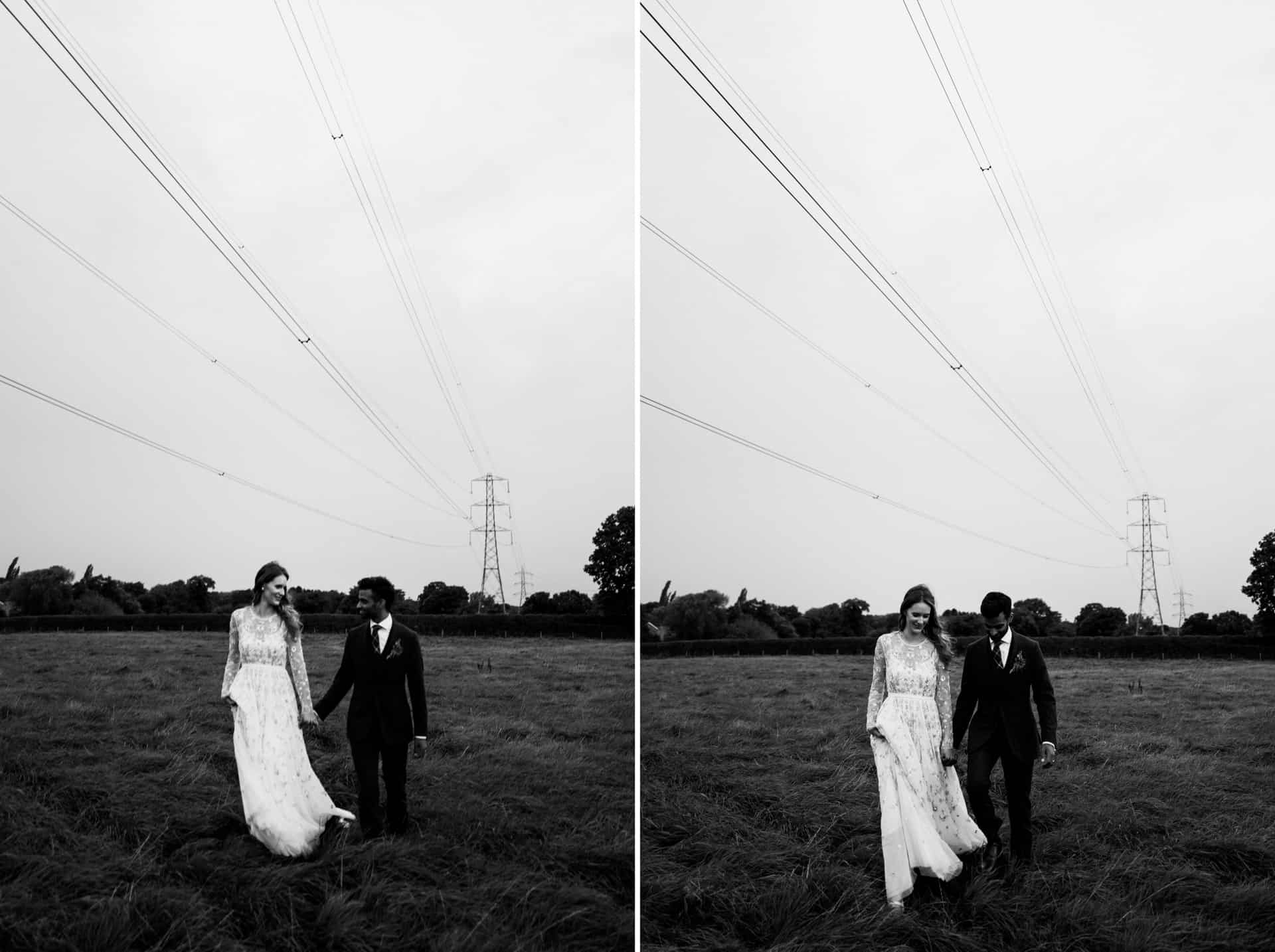 bride and groom walk in a field