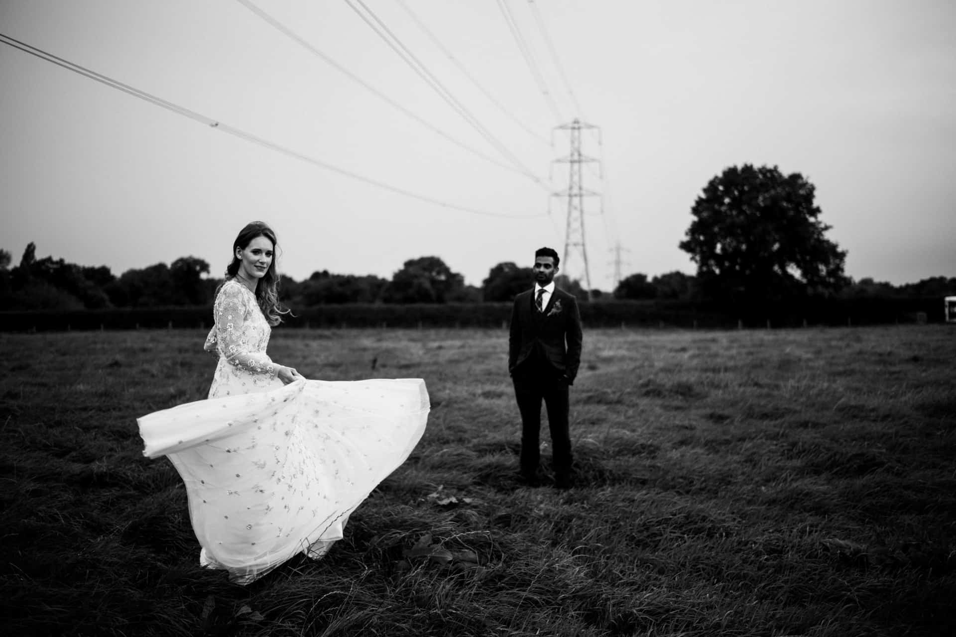 black and white shot of bride and groom in a field