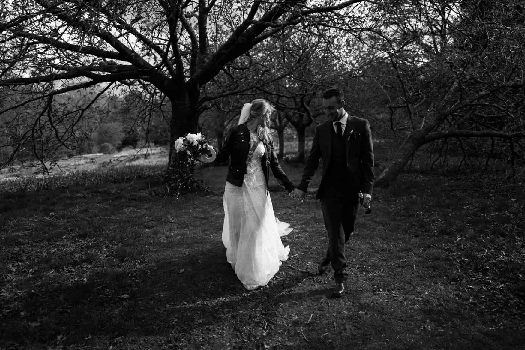 bride and groom walking in a field