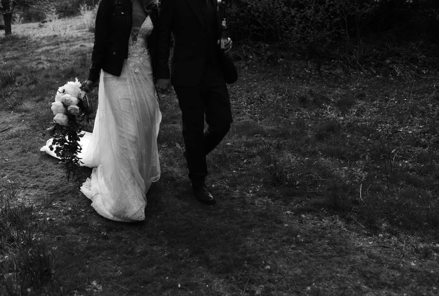 bride and groom walking in a field