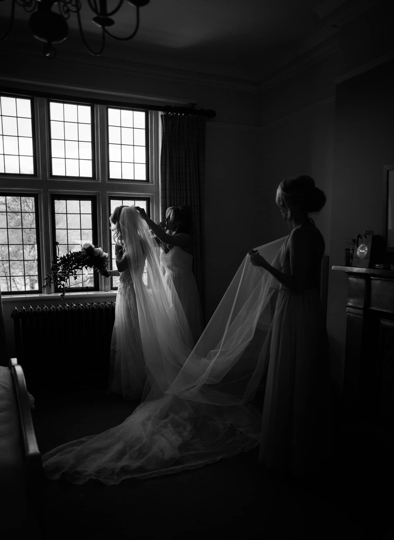 bridesmaids putting the veil on the bride