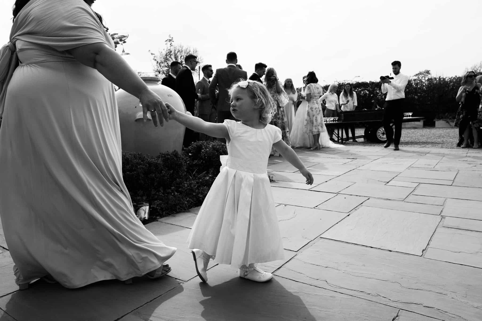 Flower girl walks with her mum