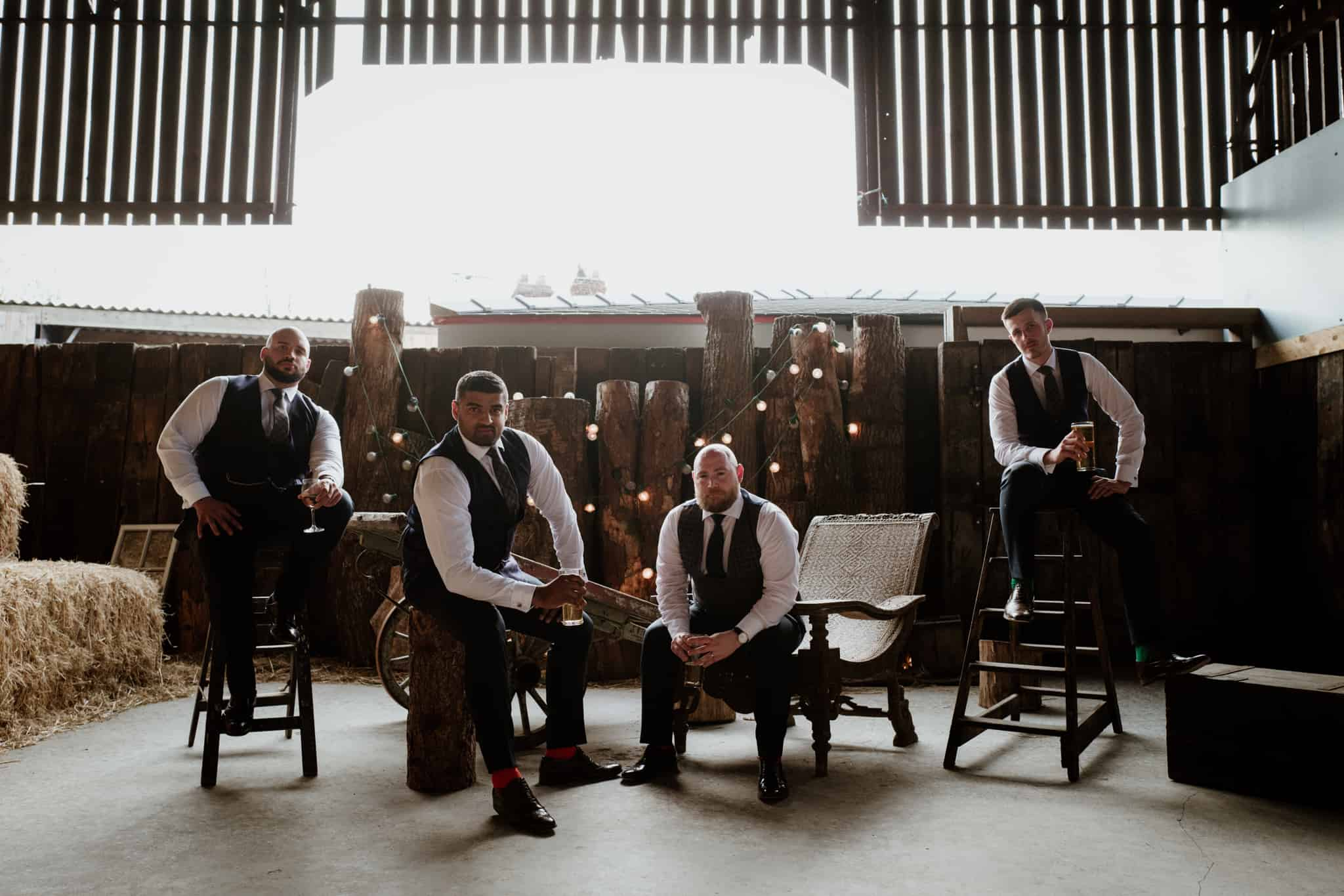 The Grooms posing in a softly lit barn
